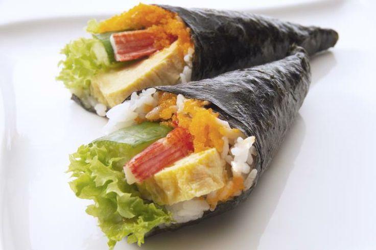 20 - Temaki  Sushi - La diferencia de este sushi con la receta anterior es que las algas nori se enrollan en forma de cucurucho. Para ello cortamos cada lámina por la mitad y luego de cada mitad cortamos triángulos. En cada triángulo ponemos una bolita de arroz y sobre este, en el centro, el resto de ingredientes cortados en bastoncitos. En este caso, hemos utilizado palitos de surimi, huevas de trucha, lechuga y tortilla francesa. Enrollamos bien, fijamos los extremos con un poco de agua