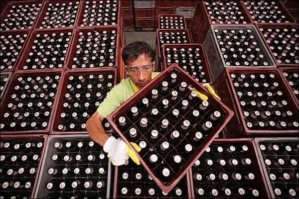 Un trabajador coloca ordena las cajas de cerveza para su distribución.