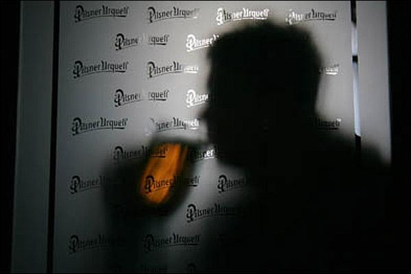 Una persona tona su cerveza en un bar.