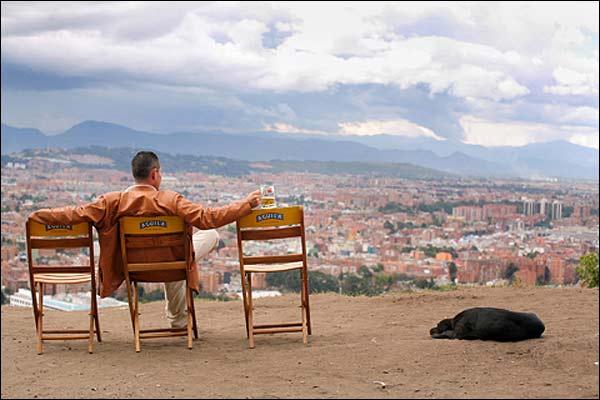 Un hombre disfruta de la vista de Bogotá con una cerveza.